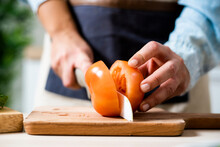 Hands Of Woman Slicing Tomato On Cutting Board