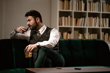 Portrait Of Bearded Man Relaxing On Sofa With Smoking Pipe And Glass Of Whiskey