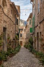 Spain, Mallorca, Valldemossa, Potted Plants Placed Along Empty Cobblestone Alley