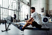Sportsman Looking Away While Sitting On Rowing Machine