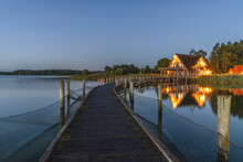 Germany, Schleswig-Holstein, Hemmelsdorf, Empty Pier On Shore OfHemmelsdorferSee Lake At Dawn With House In Background