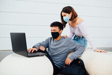 Young Couple Wearing Face Mask Using Laptop While Sitting By White Concrete Ball Against Wall