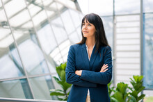 Thoughtful Businesswoman With Arms Crossed Looking Away In Office