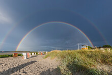 Double Rainbow Arching Over Hooded Beach Chairs Standing On Sandy Beach
