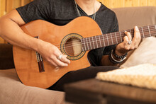 Man Playing Acoustic Guitar While Sitting At Home