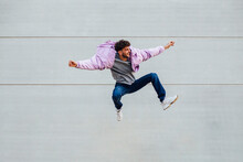 Young Man Jumping Happily Against Wall