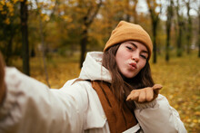 Beautiful Young Woman Blowing Kiss While Taking Selfie In Autumn Park