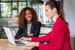 Smiling businesswoman working with colleague on laptop in office cafeteria