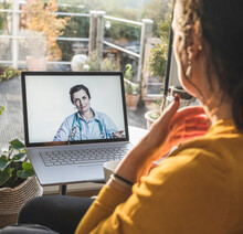 Female Doctor Smiling On Laptop Screen During Video Call