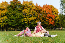 Mature Woman Lying On Female Friend's Lap On Grass At Autumn Park