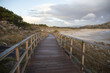 Wooden bridge near the sandy beach on a cloudy day