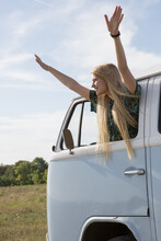 Young Woman Leaning Out Of Campervan With Arms Raised