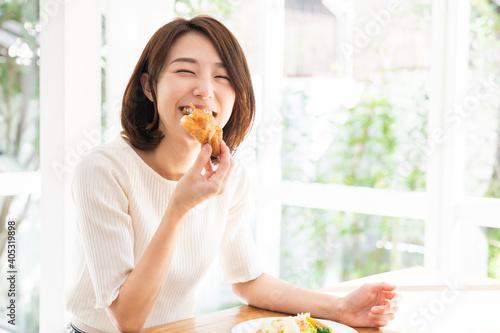 Fototapeta サラダとパンを食べる女性