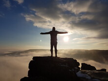 Rear View Of Silhouette Man With Arms Outstretched Standing On Rock Against Sky During Sunset