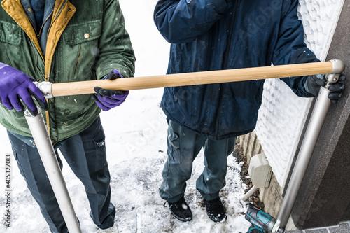 Canvastavla 雪降りの中での玄関外階段手摺取り付け工事手すり棒組付け