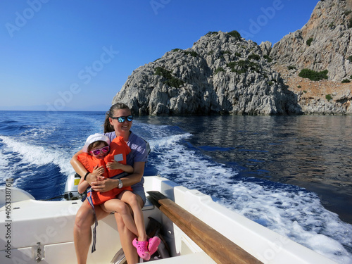 Fototapeta Smiling Woman With Daughter Sitting On Motorboat Sailing In Sea