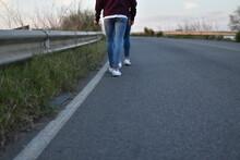 Low Section Of Friends Walking On Roadside