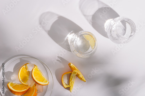 Drinking natural water and ice in beautiful glass glasses and slice of  fresh orange on plate on white background. Summer minimal flat lay with hard shadows.