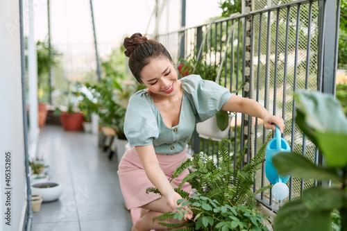 Stampa su Tela Portrait of beautiful woman watering green plants on the balcony, small cozy gar
