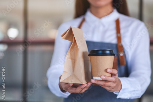 Obraz A waitress holding and serving paper cup of coffee and takeaway food in paper bag to customer in a shop - fototapety do salonu