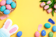 Happy Easter. Multi-colored Eggs In A Basket, Rabbit Ears With A Protective Mask, A Bouquet Of Tulips On A Yellow Background. Flat Lay Greeting Card With Copy Space.