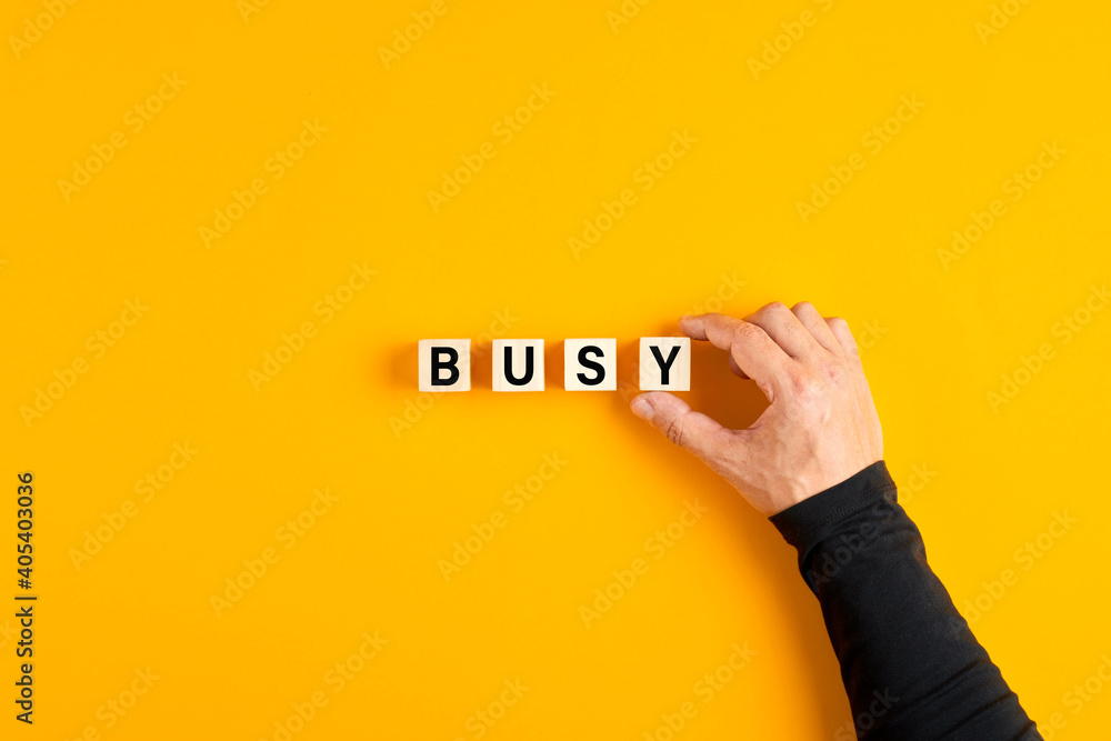 Fototapeta Male hand placing the wooden cubes with the word busy on yellow background. Overwork, stress or occupied