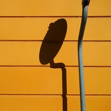 Close-up Of Shadow Of Satellite Dish On Orange Wall