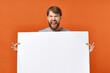 canvas print picture - happy guy with mockup in hand poster orange background Copy Space