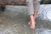 Legs Of A Woman In Pants Who Sitting On A Wood Bridge And Swinging Her Feet In A River