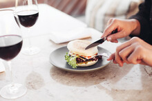 Eating Burger In A Restaurant With Fork And Knife. Two Glasses Of Red Wine On A Marble Table