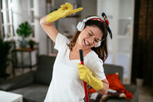 Young Attractive Woman Cleaning Home. Happy Beautiful Woman Listetning The Music, Enjoying In Cleaning