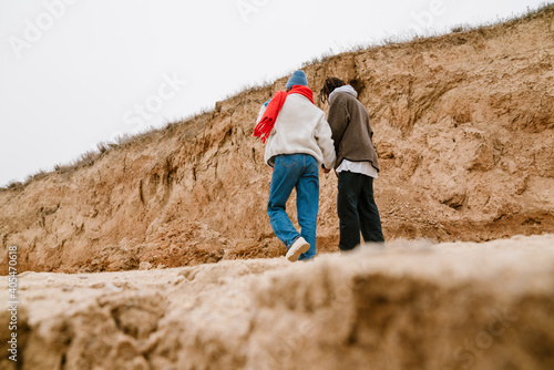 Attractive young multiethnic couple walking at the beachside Fototapeta