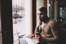 Young Man Drinking Coffee And Working On Laptop