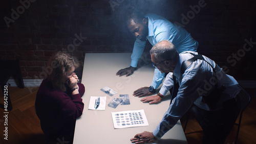 Vászonkép Two police officers and woman criminal in interrogation room