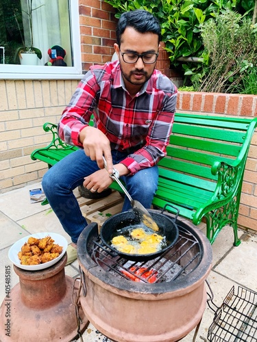 Man Preparing Food On Barbecue Grill In Yard