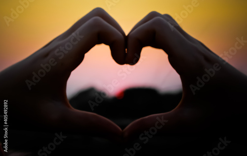Obraz Cropped Hands Of Woman Making Heart Shape Against Clear Sky During Sunset - fototapety do salonu
