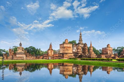 Fototapeta Buddha statue and pagoda Wat Mahathat temple with reflection, Sukhothai Historic