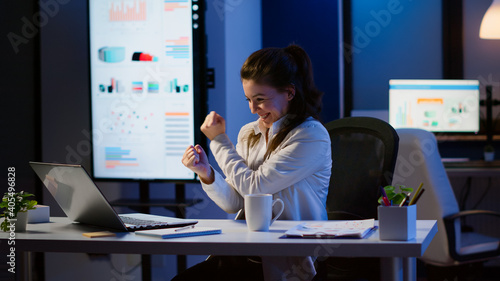 Obraz na plátne Excited woman feel ecstatic reading great online news on laptop working overtime in start up company office