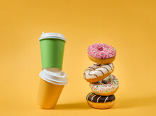 Two Paper Cups And Several Donuts On A Yellow Background With Copy Space.