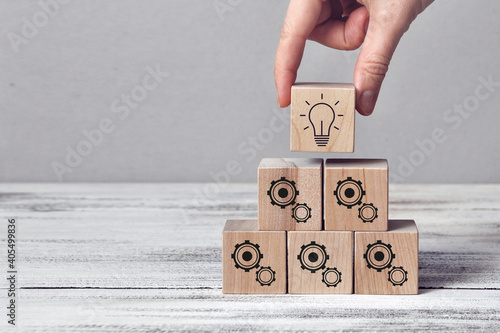 Fototapeta Wooden cubes with the image of gears and a burning light bulb
