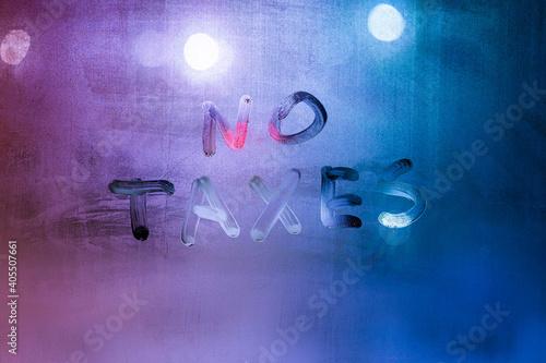 words no taxes handwritten on night wet window glass surface Fototapet