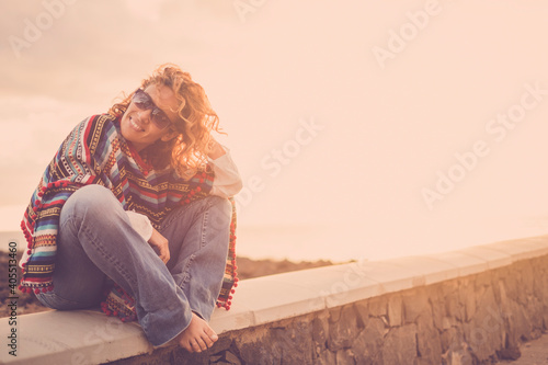 Obraz Woman sit down outdoor enjoying sunset and freedom alone with a smile - portrait of cheerful female caucasian people with trendy clothes and mixeican style poncho - fototapety do salonu