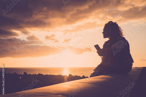 Obraz na plátne Tourist people enjoy sunset and beach on the coast sending message with a phone