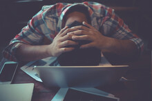 High Angle View Of Tired Businessman Sleeping By Laptop On Desk In Office