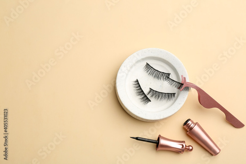Obraz Flat lay composition with magnetic eyelashes and accessories on beige background. Space for text - fototapety do salonu