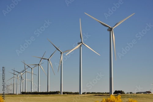 Windmills On Field Against Clear Sky