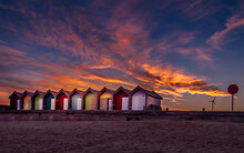 Colorful Vibrant Beach Huts And Promenade On The Seafront With Beautiful Cloudy Sunset Behind. Blyth, Northumberland, UK. British Tourism Destination.