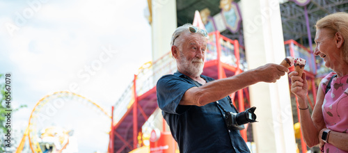 Obraz senior old couple celebration for Valentine's Day at Amusement theme park enjoying freedom relaxing, grandmother and grandfather smiling and fun, time to date and married - fototapety do salonu