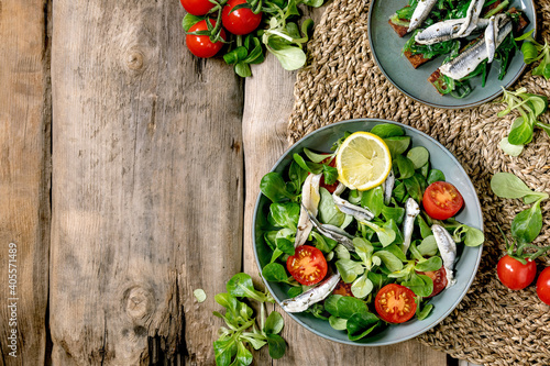 Canvas Green field salad with pickled anchovies or sardines fillet, and cherry tomatoes, served in blue bowl with lemon and olive oil on straw napkin over old wooden background