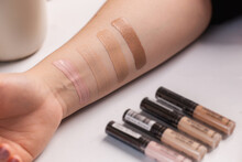 Woman Testing Different Shades Of Liquid Foundation On Her Hand And Tubes With Concealer Closeup.